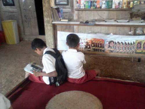 Dua anak Sekolah Dasar sedang memilih buku untuk dibaca