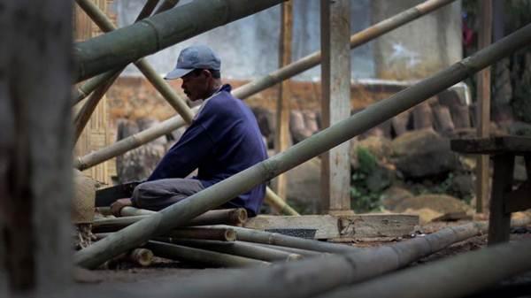 Seorang tukang memotong bambu untuk rusuk perpustakaan